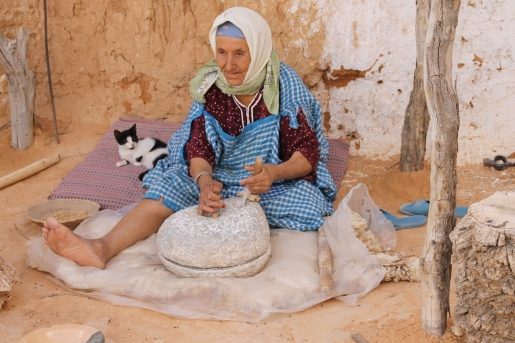 Tunisian old lady grinding grains for flour