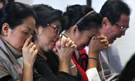 Relatives of Flight QZ8501 praying. Image courtesy of theguardian.com