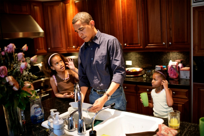 US Senator Barack Obama and his daughters (left) Malia, 8, and Sasha, 5, clean the dishes after breakfast at their home in Hyde Park - a suburb of Chicago, IL. The girls were getting ready to go to school.